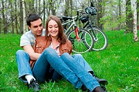 Young couple resting in a park, bicycles on background