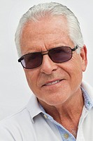Portrait of senior man with sunglasses, smiling.