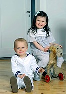 Siblings, boy, 2, and girl, 5, wearing sailor outfits