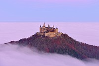 Burg Hohenzollern castle, in morning light, mist, with autumn forest, Schwaebische Alb, Swabian Alb, Baden-Wuerttemberg, Germany, Europe