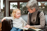 Grandmother reading a book to her granddaughter