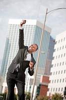 Excited Black businessman with phone in hand leaps in their air