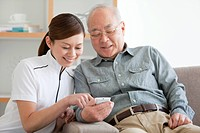 Senior Male Patient and Nurse Looking at Mobile Phone