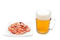 Fresh, cold beer in glass and fried prawns on plate. Isolated on white background
