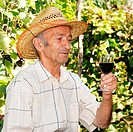 Senior smiling viticulturist holds wineglass
