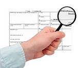 Man´s Hand Holding Magnifying Glass over 1099 Tax Form