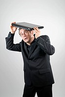 Businessman wearing a black suit seeking protection underneath his laptop which he uses as a roof