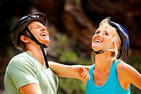 Cute couple with cycling helmets laugh together and have fun outdoors