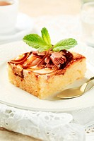 Slice of sponge cake topped with curd cheese and chocolate