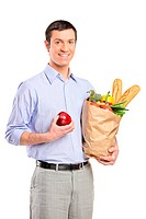Smiling man holding an apple, a bag full with bread and vegetables isolated on white background