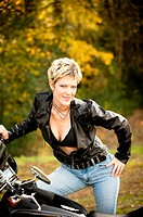 Portrait of a 41 year old blond woman looking at the camera leaning on a motorcycle