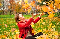 Beautiful young woman in autumn park with the leaves