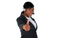 A attractive business woman wearing a headset and and giving the thumbs up, isolated on a solid white background.