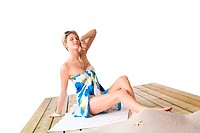 Beach _ woman sunbathing with pareo and sunglasses sitting on wooden deck