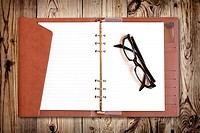 Eyeglasses on notebook isolated on wood texture
