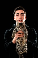 young man holding little kitten on dark background