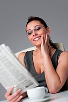 Thoughtful successful businesswoman read newspaper at office with morning coffee