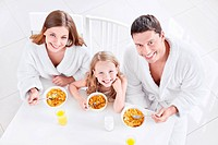 A happy family with a child eating breakfast