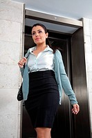 Low angle view of confident female entrepreneur stepping out of elevator