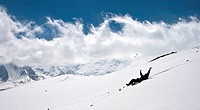 Man on snow under blue sky with clouds.