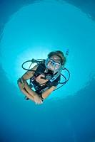 Adult Female scuba diver in bikini diving in shallow tropical water