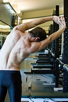 Barechested man stretching in weight room, rear view