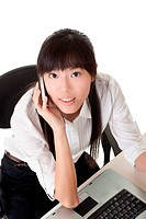 Beautiful business woman using cellphone and looking at camera in office.