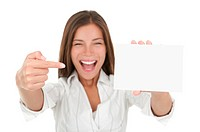 Woman pointing excited at blank card sign with copy space. Woman in white shirt isolated on white background
