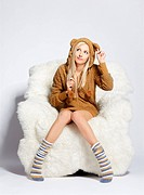 portrait of beautiful blonde girl in brown plush hud with bear ears sitting on big white furry arm_chair