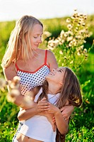 Beautiful mother and daughter family playing on meadow in sunset sun beams