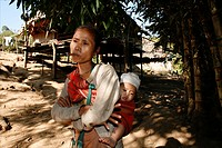 A Burmese woman carrying a baby stands in front of a hut in the village for displaced people In Myanmar Burma, thousands of people have settled near t...