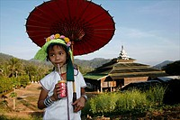 A young Longneck girl stands in front of a temple, drinking a Coke and holding a red parasol Approximately 300 Burmese refugees in Thailand are member...