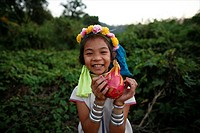 Laughing Longneck girl holding fruit Approximately 300 Burmese refugees in Thailand are members of the indigenous group known as the Longnecks The lar...