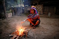 A young Longneck girl watches over a fire Approximately 300 Burmese refugees in Thailand are members of the indigenous group known as the Longnecks Th...