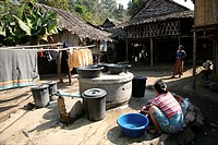 A refugee woman washes clothes in the camp Around 130,000 Burmese refugees have settled in Thailand due to opression in their homeland of Myanmar Burm...