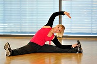 Young woman stretching, warming up exercises, Haus des Sports, House of Sport, SpOrt, Stuttgart, Baden_Wuerttemberg, Germany, Europe