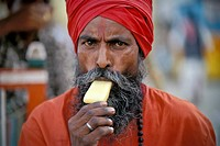 Sadhu with a red turban eating an ice cream, Kashi, Varanasi or Benares, Uttar Pradesh, North India, India, Asia