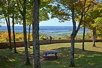 Couple sitting on stone masonry guardrail overlooking the Ottawa River, Gatineau Park, Gatineau, Quebec, Canada.