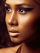 Exotic closeup beauty portrait of a young beautiful woman´s fac eof Pacific Islander ethnicity with golden skin and artistic makeup