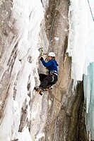 Young woman climbs a mix of ice and rock while ice_climbing in Banff National Park near Banff, Alberta, Canada.