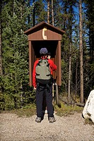Hiker calling on outdoor pay phone, Jasper National Park, Alberta, Canada.