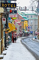 Tourists walking on an old street with Heritage commercial buildings in the Old Quebec in winter during a snowfall, Quebec, Canada