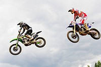 Two motocross riders, 101 and 10, are airborne after a jump at the Monster Energy Motocross Nationals at the Wastelands track in Nanaimo, BC.