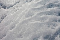 Wind and thaw_freeze cycles created patterns on surface of packed snow.