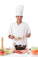 Young cheerful nepalese man chef cooking oriental food in wok. Fresh ingredients on table. Studio shot. White background.