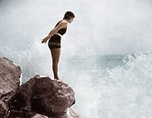 Female swimmer on rock above crashing surf All persons depicted are not longer living and no estate exists. Supplier warranties that there will be no ...