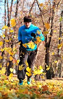 Image of a man running between falling leaves in a park in autumn.
