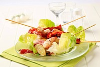 Roasted chicken skewers and bacon served on lettuce leaves