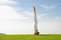 Young woman practising Hatha yoga outdoors, showing the pose sirshasana, head stand, Nove Mesto, Okres Teplice, Czech Republic, Europe