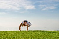 Young woman practising Hatha yoga outdoors, showing the pose parshva kakasana, parshva bakasana, sideward crow pose, sideward crane pose, Nove Mesto, ...